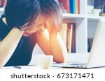 Small photo of Headache Business Woman Working on Laptop in the Office, Soft focus. Thoughtful officer put her hands on head for relax. Jaded, Toilsome, Exhausted Worker in workplace. Fatigue and fail concept