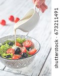 a hand pouring dressing onto... | Shutterstock . vector #673211491
