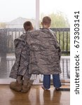 Two young boys wearing parents military uniform look out of a raining window