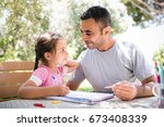 Little Girl And Father Drawing Pictures Together Outdoors In Summer - stock photo