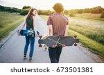 skateboarding couple having fun ... | Shutterstock . vector #673501381