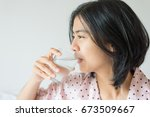 asian woman drinking a glass... | Shutterstock . vector #673509667