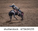 Cowboy riding a bucking bronco in a rodeo