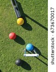 Small photo of Looking down from above on a game of croquet with a croquet mallet about to strike the yellow ball with the blue ball in the jaws of the steel croquet hoop with the black and red balls nearby.