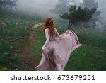 beautiful young woman in a long ...   Shutterstock . vector #673679251