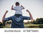 dad and son having fun outdoors. | Shutterstock . vector #673873681