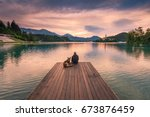 Man And Dog Sitting On Wooden...