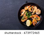 pan of grilled shrimps on a... | Shutterstock . vector #673972465