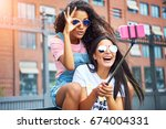 two smiling young girlfriends... | Shutterstock . vector #674004331