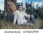Small photo of Positive man sitting on grass against a tree. Handsome guy repose in nature. Outdoors - outside. Full body