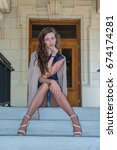 Small photo of Pretty brunette in tan pantyhose and open toe heels seated on steps with knees together.