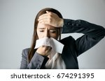 Small photo of young woman blowing her nose. allergic rhinitis. hay fever.