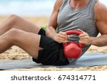 Small photo of Fitness man lifting kettlebell weight training russian twist exercise. Exercising on beach training with kettlebells working out core, obliques and abdominal abs muscles working out six pack.