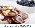 Dutch mini pancakes, or poffertjes, with butter, syrup and powdered sugar.  Fresh blueberries out of focus in the background. - stock photo