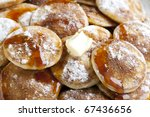 Dutch mini pancakes, or poffertjes, with butter, syrup and powdered sugar.  background. - stock photo