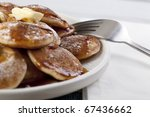 Dutch mini pancakes, or poffertjes, with butter, syrup and powdered sugar. - stock photo