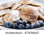 Dutch mini pancakes, or poffertjes, and fresh blueberries sprinkled with powdered sugar. - stock photo