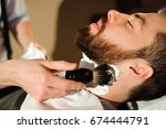 master cuts hair and beard of... | Shutterstock . vector #674444791