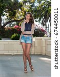 Small photo of Pretty brunette in tan pantyhose, short denim and open toe heels looking relaxed in courtyard.