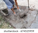 worker stirs concrete shovel | Shutterstock . vector #674525959
