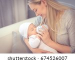 young mother feeding her little ... | Shutterstock . vector #674526007