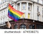 a spectator waves a gay rainbow ... | Shutterstock . vector #674538271