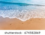 Beach  Wave And Footprints At...