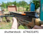 Small photo of Man aims at target by crossbow or arbalest. Ready for fire.