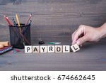 Small photo of payroll. Wooden letters on dark background