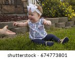 a baby sitting on the grass and ... | Shutterstock . vector #674773801