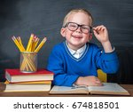 Small photo of Happy cute clever boy is sitting at a desk in a glasses with raising hand. Child is ready to answer with blackboard ona background. Back to school. Apple and books on desk. First time to school