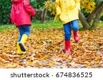 Small photo of Two little children playing in red and yellow rubber boots in autumn park in colorful rain coats and clothes. Closeup of happy kids dancing and walking through fall autumnal goden leaves and foliage.