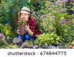 young woman gardener smelling... | Shutterstock . vector #674844775