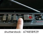 Small photo of Finger pressing the Rewind button on an old stereo 80's
