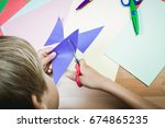 schoolboy cutting colored paper ... | Shutterstock . vector #674865235