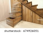 Small photo of Modern architecture interior with luxury hallway with glossy wooden stairs in modern storey house. Custom built pullout cabinets on glides in slots under stairs. Use of space for storage.