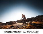 man rides bicycle in the dry... | Shutterstock . vector #675040039
