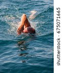 Small photo of Man swims in free style in the offshore sea, Adriatic Sea.