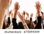 raised hands and arms of large... | Shutterstock . vector #675094549