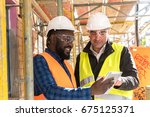 two engineers  an african... | Shutterstock . vector #675125371