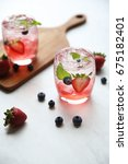 Small photo of Strawberry juice cocktail with ice and mint on white tone amd wooden