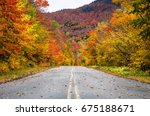 Small photo of Straight Stretch of a Mountain Road Through a Colourful Forest of Maple Trees at the Fall Foliage Peak. Adirondacks, NY.