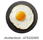 fried egg on round black slate... | Shutterstock . vector #675232405