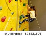 little girl climbing a rock... | Shutterstock . vector #675321505