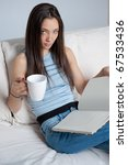 Beautiful girl sitting at home with a mug and a book - stock photo