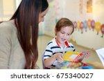 kid reading a book with teacher ... | Shutterstock . vector #675340027