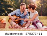 picnic time. young couple... | Shutterstock . vector #675373411