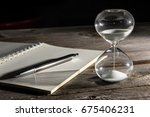 hourglasses and book on a... | Shutterstock . vector #675406231