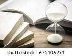 hourglass and open book on... | Shutterstock . vector #675406291