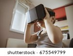 little boy using vr headset in... | Shutterstock . vector #675549799
